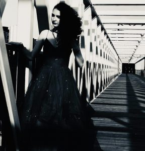 Tori Evans in a dress on a bridge in black and white